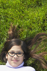 Girl wearing glasses lying in grass