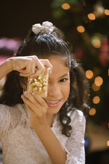 Hispanic girl holding Christmas gift in front of face