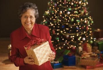 Senior Hispanic woman holding gift in front of Christmas tree