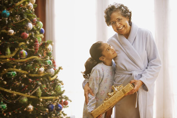 Hispanic grandmother and granddaughter on Christmas morning