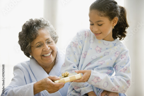 Hispanic granddaughter giving grandmother gift
