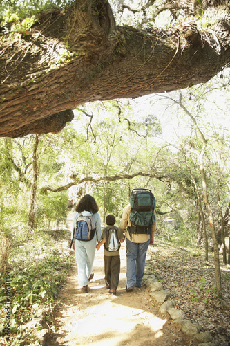 Hispanic family hiking with backpacks