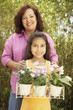 Hispanic mother and daughter with potted flowers outdoors