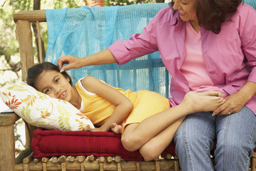 Hispanic mother and daughter on bench outdoors