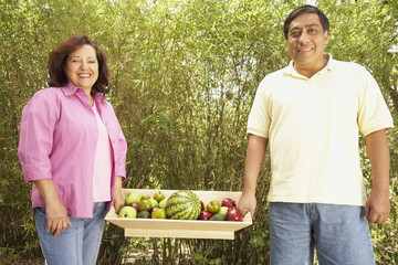 Hispanic couple carrying tray of fruit outdoors