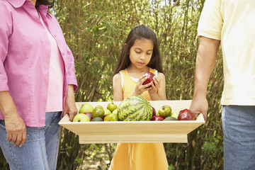 Hispanic family with tray of fruit outdoors