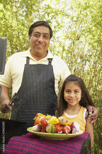 Hispanic father and daughter next to barbecue grill with kebabs