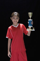 Studio shot of young Hispanic girl with soccer trophy