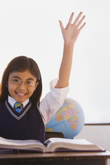 Young Hispanic girl raising hand in classroom