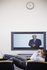 Young Asian man in chair next to television