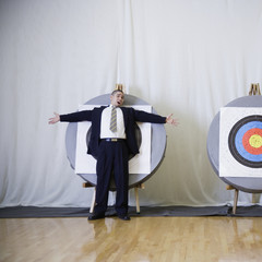 Businessman standing in front of bulls eye