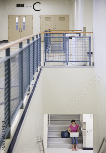 Female student with laptop on stairs