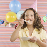 Young girl eating cake at birthday party