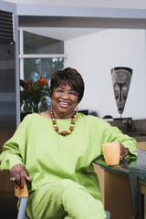 Middle-aged African woman smiling with coffee
