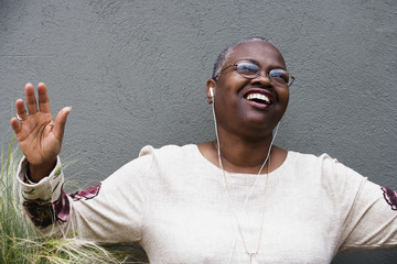 Middle-aged African woman listening to music with earphones