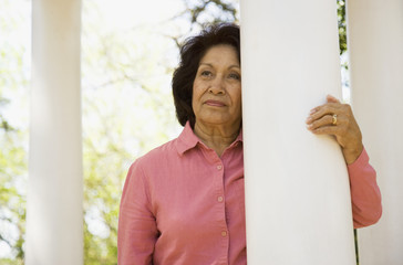 Senior woman leaning on column outdoors