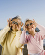 Grandmother and granddaughter holding up rocks to eyes at beach