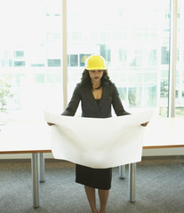 Businesswoman wearing hard had and looking at blueprints