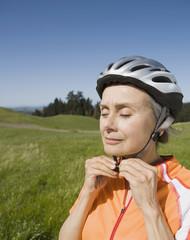 Senior woman fastening bicycle helmet