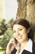 Hispanic businesswoman leaning on tree using cell phone