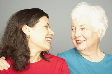 Mother and adult daughter smiling at each other