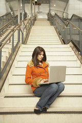Woman sitting on stairs using laptop