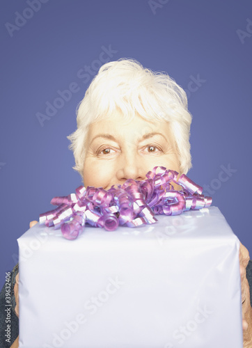 Studio shot of senior woman with gift