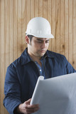 Hispanic man with hard hat and blueprints