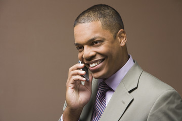 Studio shot of African businessman using cell phone