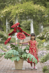 Asian girl in garden with giant potted plant