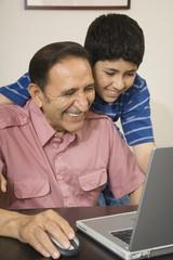 Hispanic grandfather and grandson using laptop