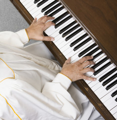 High angle view of senior man playing piano
