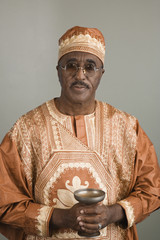 African man wearing traditional dress and holding chalice