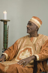 African man wearing traditional dress sitting next to lit candle