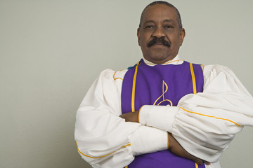 African man wearing church choir gown with arms crossed