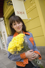 Hispanic woman with flowers on sidewalk