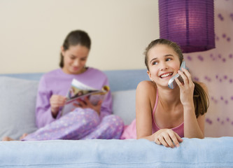 Hispanic sisters reading and using cell phone on bed