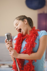 Hispanic girl singing into microphone in bedroom