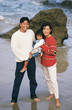Asian parents and young daughter at beach