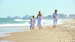 Happy Caucasian Family Running on Beach