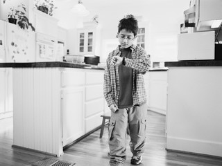Young boy looking at watch in kitchen