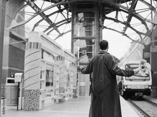 Man holding flowers with arms out at train station