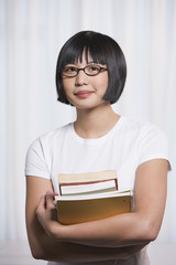 Young Asian woman holding school books