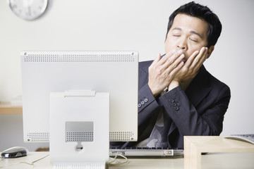 Asian businessman sitting at computer yawning