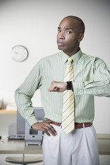 African businessman holding up watch and frowning