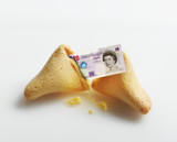 Broken fortune cookie with British Pound inside