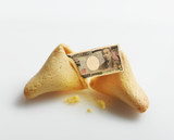 Broken fortune cookie with Yen inside
