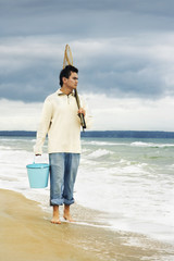 Asian man walking on beach with net and bucket
