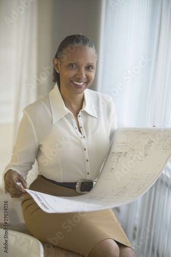 Senior African businesswoman holding blueprints