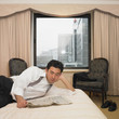 Asian businessman reading newspaper in hotel room